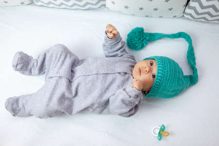 Newborn baby in knitted hat and gray pajamas