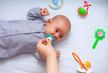 hand holds out a pacifier to a crying newborn. Selective focus