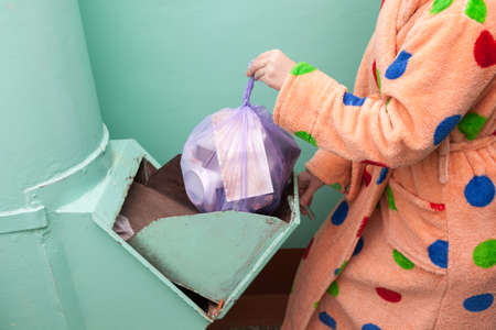 a housewife in a yellow polka dot dressing gown throws a waste bag into the chute