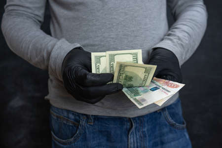 A man holds dollars and rubles in his hands
