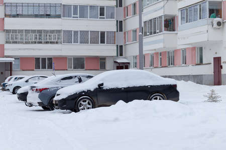 Cars in a parking lot in the city after a snowstorm. Russia, winter.