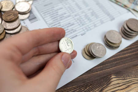 A woman holds in her hands Russian money, a piece of paper with numbers on top of a receipt for payment of utilities. Background with Russian accounts for payment and rubles.