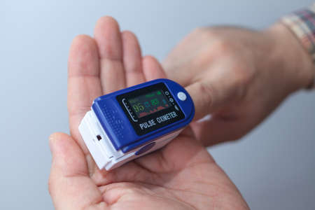 A man checks his oxygen level using an oximeter