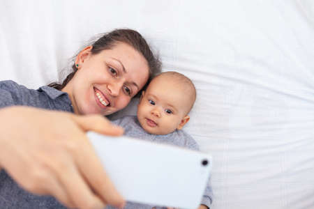 Mom with newborn baby talking on video communication while lying on the bed Stock fotó