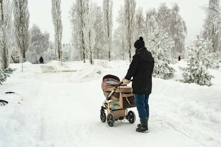 Dad with a baby carriage in winter walks in the park Stock fotó