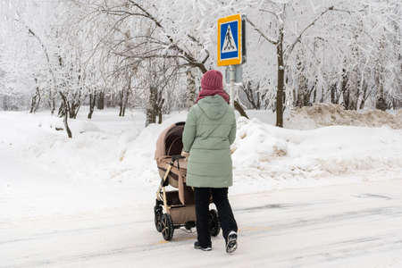 Mom with a stroller crosses the road in winter
