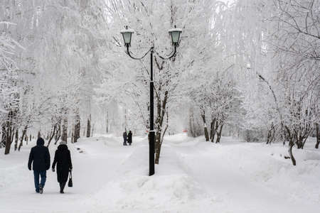People walk along the road in the city park in winter Stock fotó
