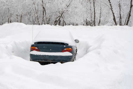 Car in the parking lot in winter, big snowdrifts around Stock fotó