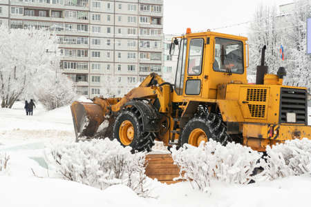 Big yellow tractor cleans snow on city streets russia