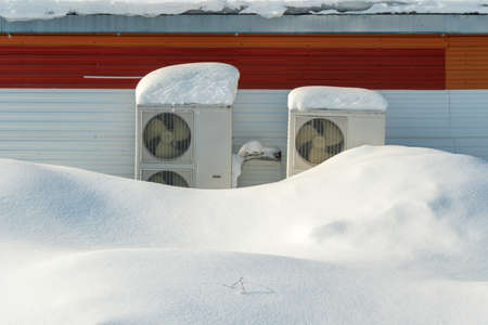 Air conditioner on the facade of an industrial building covered with snow Stock fotó