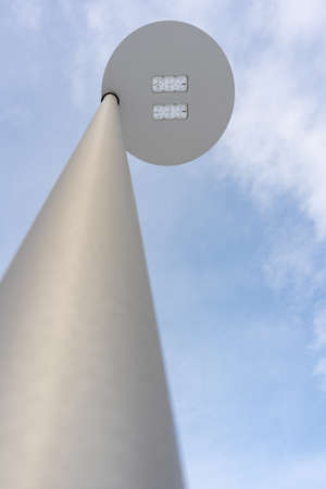 Modern LED street lamp against a blue sky, bottom view. Selective focus