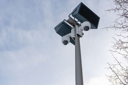CCTV cameras and loudspeakers on the background of the sky and tree branches with thorns Stock fotó