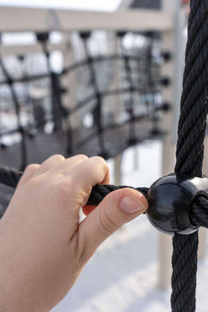 The hand holds the rope on the playground