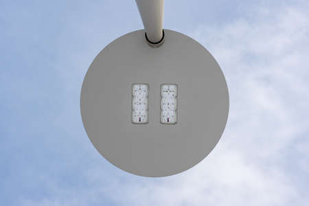 LED street lamp against a blue sky, bottom view