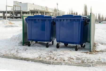 Large blue fenced dumpsters in winter