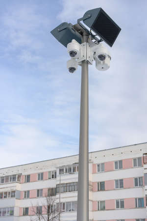 CCTV camera with loudspeakers and a megaphone against the sky and an apartment building in Russia. Stock fotó