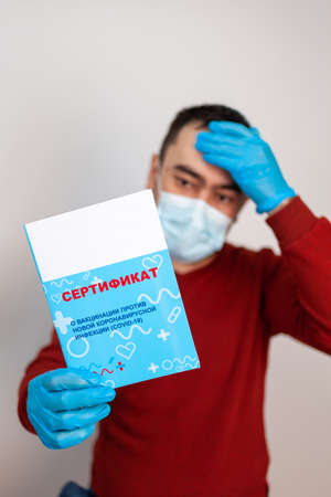 A man holds a vaccination certificate in his hands. Russia, Russian text