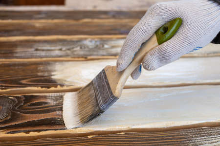 Painting a wooden background with white paint. Hand with brush