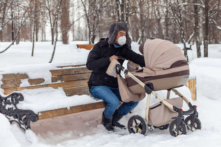 Father with a stroller is resting on a park bench. Winter Russia
