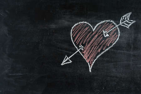 Red Heart symbol with arrow on chalkboard, love symbol. Copy space Stock fotó