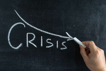 A hand with white chalk writes the word CRISIS on a chalk board