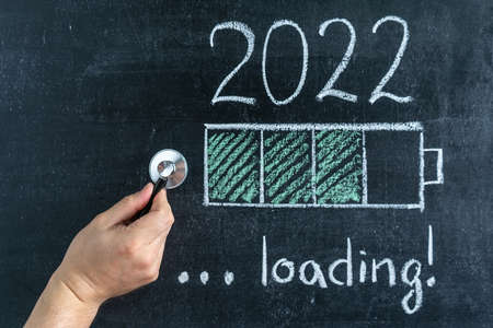 Hand with a stethoscope, a charge indicator on a chalk board and the text Loading 2022