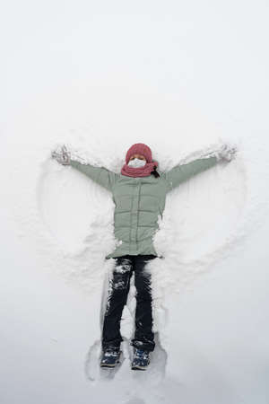 A girl in a medical mask is lying in the snow. Snow angel
