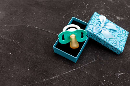 Gift box and pacifier for little boy on black background Stock fotó