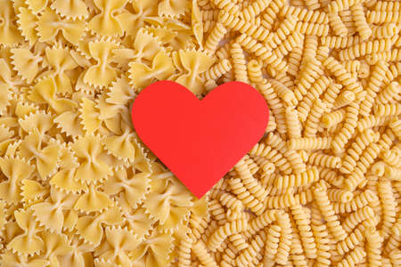 Red heart symbol on raw pasta background Stock fotó