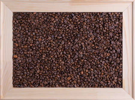 Roasted coffee beans in a wooden light frame. View from above
