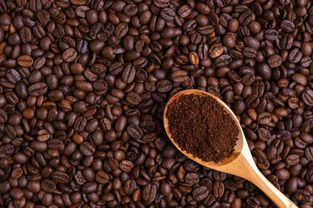 Ground coffee in a wooden spoon lies on freshly roasted coffee beans