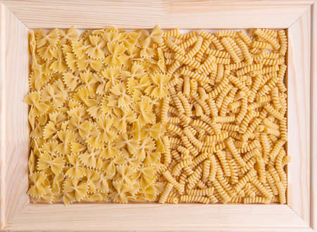 Farfalle and fusilli pasta in a wooden frame. Top view