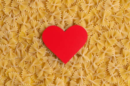 Red heart on the background of farfalle pasta, top view Stock fotó
