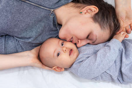 Happy mom kisses baby while lying on the bed, top view Stock fotó