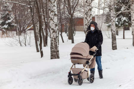 Winter walk with a newborn in a baby carriage. Father with a baby carriage in the park.