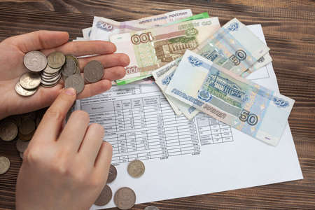 A woman holds in her hands Russian money, a piece of paper with numbers on top of a receipt for payment of utilities. Background with Russian accounts for payment and rubles. Banque d'images