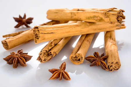 Group of cinnamon sticks with star anise and polish on white background