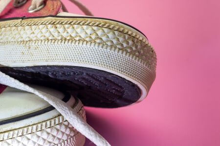 Female Pink canvas vintage styled and dirty basketball shoes parrtial close-up. girl freedom and independence. Stock Photo