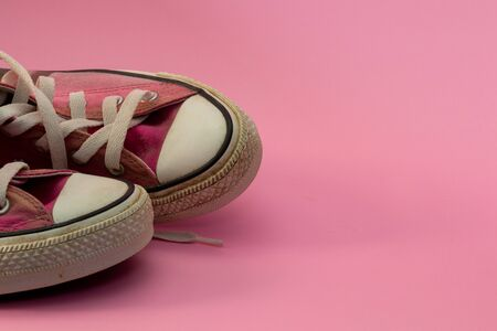 Female Pink canvas vintage styled, dirty and gold painted basketball shoes parrtial close-up. girl freedom and independence. Text Space. Stock Photo