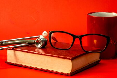 Infant stethoscope, book, glasses, red cup, red background. Medical reading concept, lady doctor reading.
