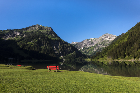 Red bench on Lake Vilsalpsee at Tannheim, Vilsalpsee mountains, Tannheim valley high valley, Tyrol, Austria, Europe