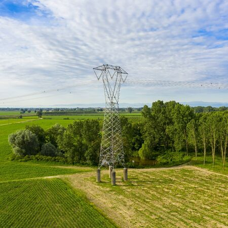 electricity tower with high voltage cable in a wonderful field