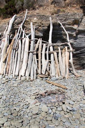 provisional: Choza provisional hecha con un trozo de madera viejos en el mar Foto de archivo