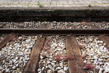 red grass: Train track with platform and red grass on them Stock Photo