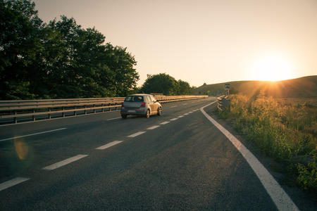 toward: Car going toward the sunset on a soft Tuscany hill, driving in the freeway Stock Photo