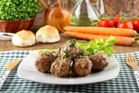 Meatballs stewed with vegetables on complex background photo