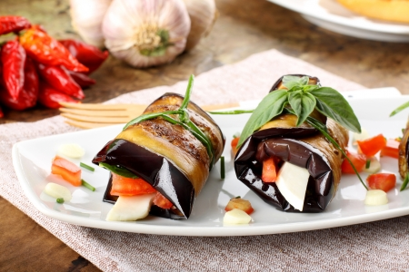 Eggplant rolls with cheese, tomato and basil on complex background photo