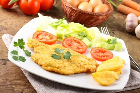 Chicken cutlet with salad on complex background photo
