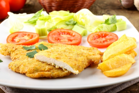 breaded: Chicken cutlet with salad on complex background