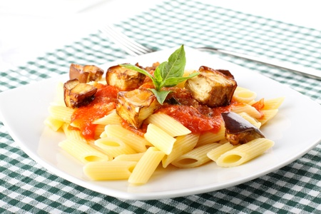 penne: Pasta with tomato, basil and eggplant on complex background